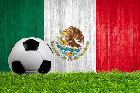 Soccer ball on grass with Mexico flag background close up photo