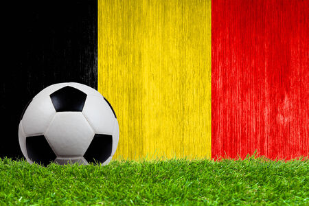 Soccer ball on grass with Belgium flag background close up photo