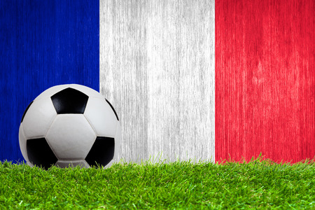 Soccer ball on grass with France flag background close up photo