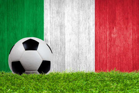 Soccer ball on grass with Italy flag background close up photo