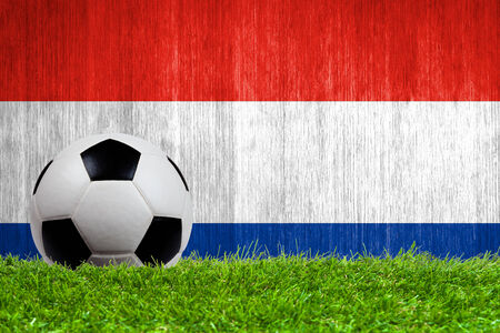 Soccer ball on grass with Netherlands flag background close up photo