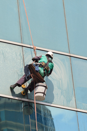 A worker cleaning windows service on high rise building photo