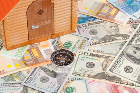 Plastic house on a pile of money photo