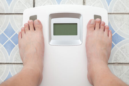 weight machine: Man steps on digital weight machine Stock Photo