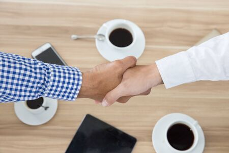 Asian businessmen handshake while having coffee, top view