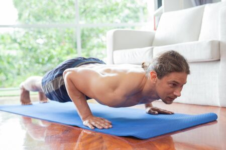 Close up of young man doing push up exercise on mat in living room at home