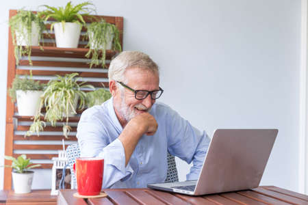 Senior retirement man is enjoy chating with someone using his laptop at home and feeling happy 免版税图像