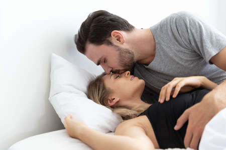 Caucasion couple on bed and man kiss women on her forehead Stock Photo