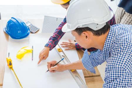 Group of architects woking on blank blueprint