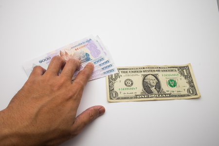 A hand placing KHR Bank notes around the 1 USD