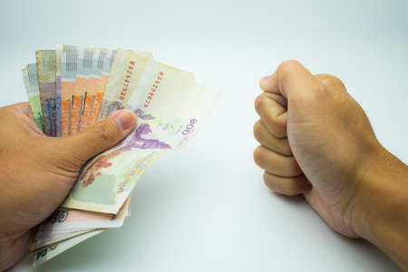 A hand holding KHR bank note with a fist