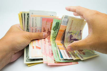 Hands holding bank notes in USD THB SND and KHR Stock Photo