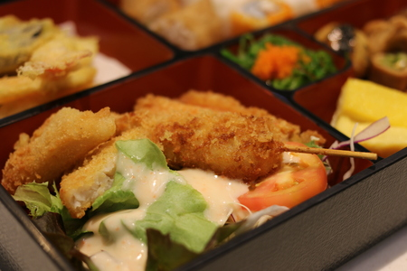 bento box: Japanese food in bento box with fried chicken, fish, squid, salad and tempura
