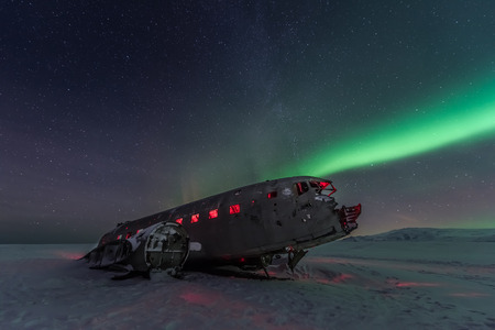 wreck: northern lights over plane wreck on the wreck beach in Vik, Iceland