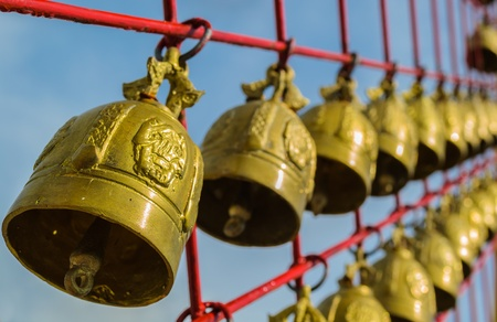 Many of holy bells are hanging on the red net in a buddhist temple