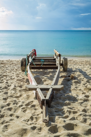 A wooden cart for carry a small boat is on the beach photo