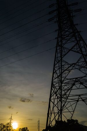 A silhouette of high- voltage tower with sunset photo