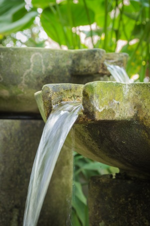 moistness: Flowing water from stone basin in the garden