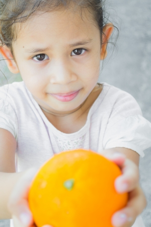 A smiling cute girl is giving an orange to adult