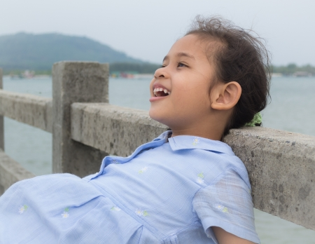inattention: A cute joyful girl on the bridge with sea view