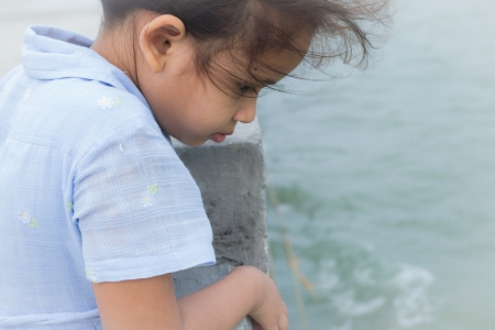 inattention: A cute girl is staring to the sea on a bridge with strong wind Stock Photo