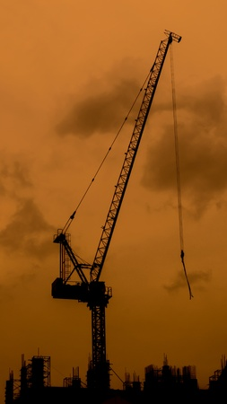 High crane on the top of the construction in the evening photo