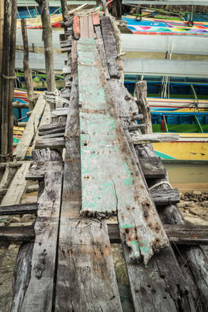 An old grunge wooden bridge at the pier when low tide photo