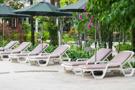 couches with umbrellas are arrange in row in the garden Stock Photo - 22718874