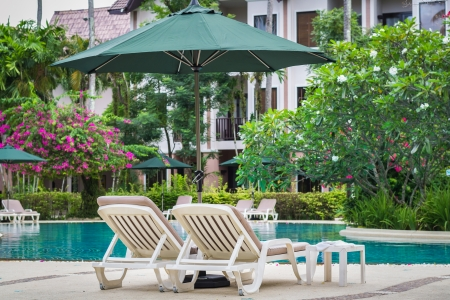 couches with umbrellas around the pool in the resort Stock Photo - 22718875