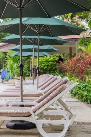 couches with umbrellas around the garden in the resort Stock Photo - 22718876