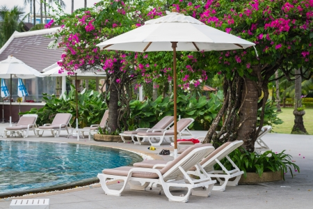 couches with umbrellas around the pool in the resort Stock Photo - 22718877