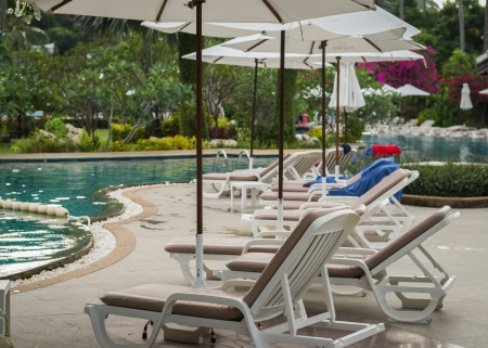 couches with umbrellas around the pool in the resort Stock Photo - 22718878