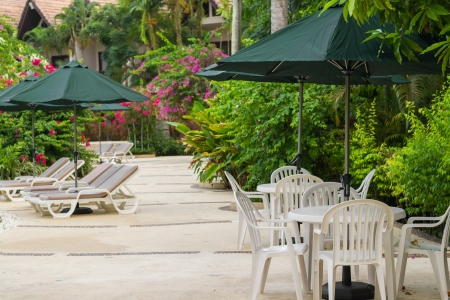 couches with umbrellas around the garden in the resort Stock Photo - 22718507