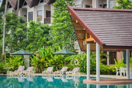 couches with umbrellas around swimming pool in the resort Stock Photo - 22718504