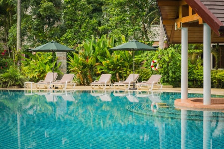 couches with umbrellas around swimming pool in the resort Stock Photo - 22718062