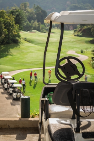 Golf club cars at golf field with golfers are on started point photo