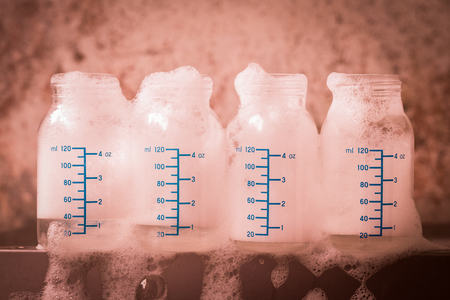 bottle of milk with toxic washing liquid and grunge background photo