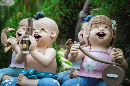 baked clay dolls playing musical instrument in the garden photo