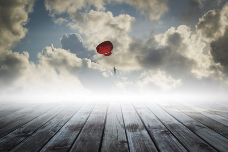 parachute on the sky with wooden floor, success concept photo