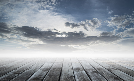 wooden plank floor with cloudy blue sky photo