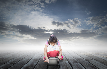 lonely cute girl using digital tablet on wooden floor under cloudy blue sky photo