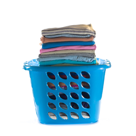 Laundry basket with folded clothes over white background Stockfoto