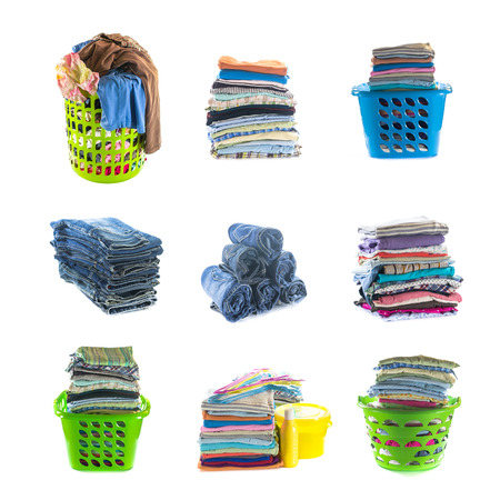 stacks of clothing collection with basket, clothes hanger, washing powder and liquid isolated on white photo