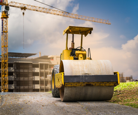 Road roller at construction site with cloudy blue sky photo