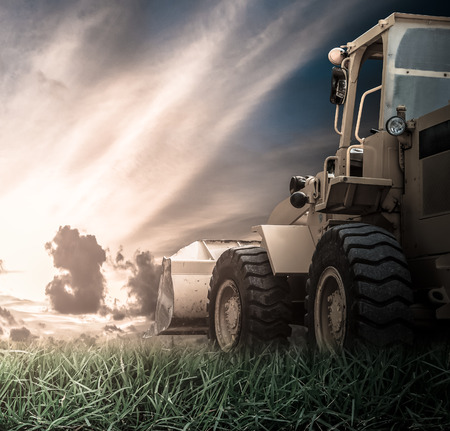Yellow tractor in a field during sunrise Stockfoto