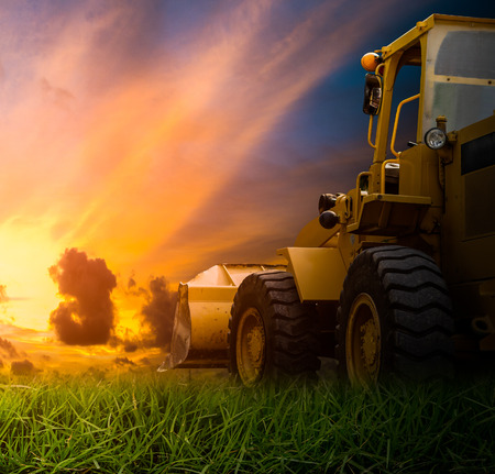 Yellow tractor in a field during sunrise photo