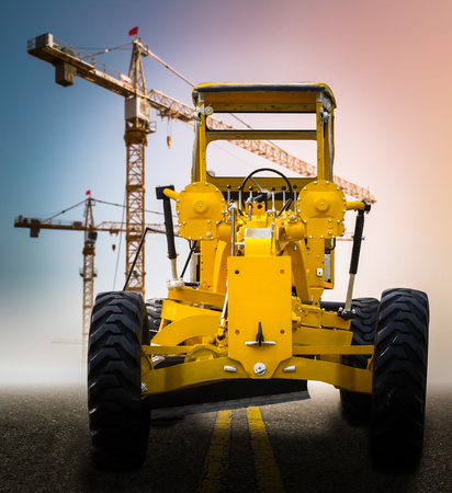 old yellow motor grader on the road at construction site photo