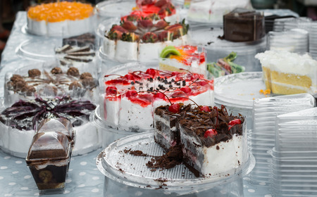 Various flavor of cake on the table with plastic container