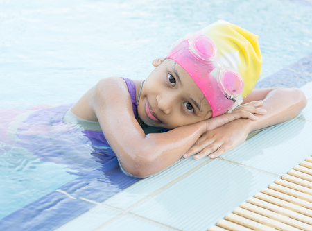 be wet: Little girl is wearing goggles and cap in swimming pool
