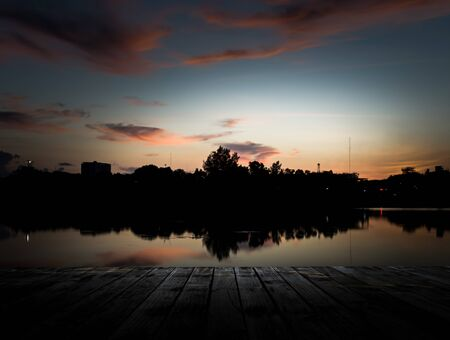 Scenery of the wooden pier with dramatic sky above the pond in urban photo